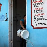 Waitress tossing out water into the street in Baja
